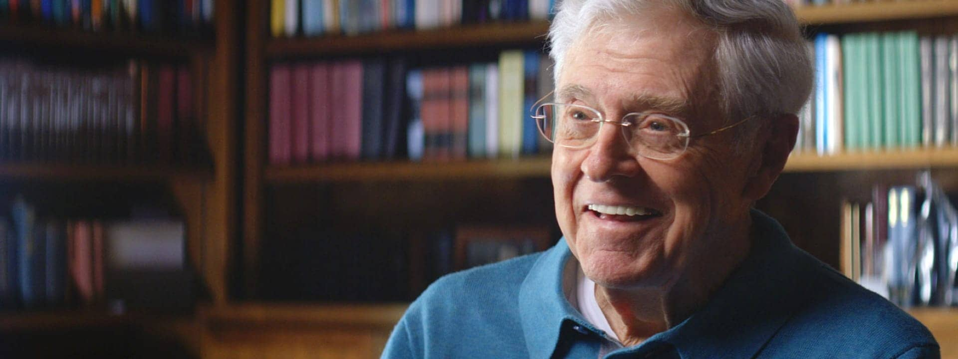 Charles Koch in front of a book shelf